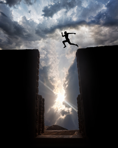 Man Silhouette jumping over the abyss at sunset cloudy sky background